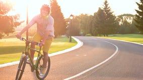Bicicleta del montar a caballo del individuo en el camino almacen de metraje de vídeo