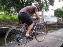 Bicicleta del montar a caballo a lo largo del pequeño río Foto de archivo libre de regalías