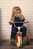 Bicicleta del montar a caballo del muchacho en sitio Niño y triciclo Imagen de archivo libre de regalías