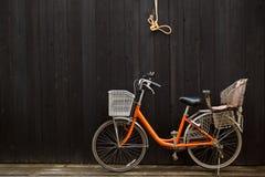 Bicicleta del ocio delante de la cerca de madera negra Imagen de archivo libre de regalías