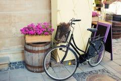 Bicicleta del vintage con la cesta de la flor y tablero de tiza cerca del café Imagenes de archivo