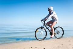 Bicicleta deportiva adolescente joven del montar a caballo de la muchacha en la playa Foto de archivo libre de regalías