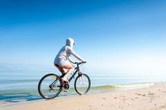 Bicicleta deportiva adolescente joven del montar a caballo de la muchacha en la playa Foto de archivo