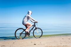 Bicicleta deportiva adolescente joven del montar a caballo de la muchacha en la playa Fotografía de archivo