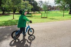 Bicicleta do equilíbrio da equitação do rapaz pequeno Imagens de Stock Royalty Free