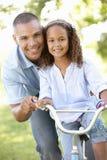Bicicleta do passeio de Teaching Daughter To do pai no parque Imagem de Stock