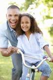 Bicicleta do passeio de Teaching Daughter To do pai no parque Foto de Stock Royalty Free