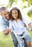 Bicicleta do passeio de Teaching Daughter To do pai no parque Fotografia de Stock