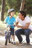 Bicicleta do passeio de Teaching Son To do pai Foto de Stock Royalty Free