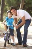 Bicicleta do passeio de Teaching Son To do pai Fotos de Stock Royalty Free