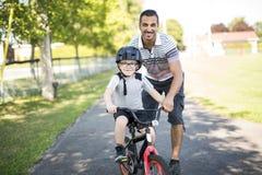 Bicicleta do passeio de Teaching Son To do pai Imagens de Stock