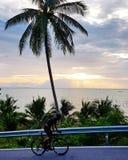 Bicicleta do passeio perto do mar contra o céu do por do sol Imagem de Stock