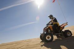 Bicicleta do quadrilátero da equitação do homem no deserto Foto de Stock