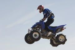 Bicicleta do quadrilátero da equitação do homem no meio do ar contra o céu Imagens de Stock Royalty Free