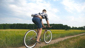 Bicicleta do vintage da equitação do homem novo na estrada rural sobre o campo Ciclismo desportivo do indivíduo ao longo da fuga  vídeos de arquivo