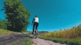 Bicicleta do vintage da equitação da jovem mulher ao longo de uma estrada rural em uma vila vídeos de arquivo