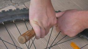 Bicicleta dos pneus dos reparos do ciclista ou do mecânico Feche acima das m?os e bicycle o pneum?tico do pneu liso filme