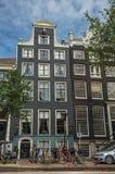 Bicicleta e carro na frente das portas de entrada de construções à moda em Amsterdão Fotografia de Stock