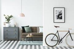 Bicicleta e cartaz na parede em uma sagacidade moderna do interior da sala de visitas imagens de stock royalty free