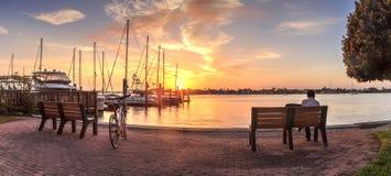 A bicicleta e o homem sentam-se em um banco na ruptura do nascer do sol do alvorecer sobre o porto da baía da fábrica imagens de stock