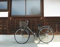 Bicicleta en la pared de madera de la casa del vintage Imagenes de archivo