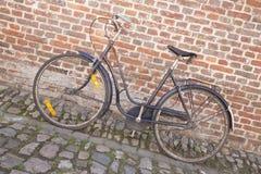 Bicicleta en piedra del adoquín contra la pared de ladrillo Imagen de archivo
