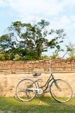 Bicicleta en viejo fondo de la pared de ladrillo Fotografía de archivo libre de regalías