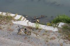 A bicicleta encontra-se no rio na água enlameada no cais foto de stock