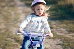 Bicicleta engraçada pequena da equitação da criança foto de stock