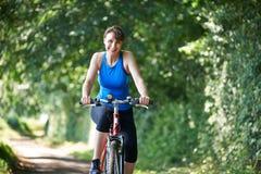 Bicicleta envelhecida meio da equitação da mulher através do campo Fotos de Stock Royalty Free