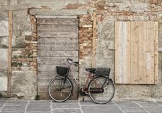 A bicicleta est? estando nas paredes pitorescas da casa velha foto de stock royalty free