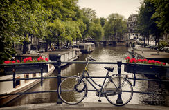 Bicicleta estacionada na ponte pedestre que negligencia um canal em Amsterdão fotografia de stock royalty free