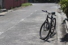 Bicicleta estacionada na rua Fotos de Stock