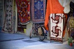 A bicicleta estacionou na frente de uma loja do tapete em Atenas, Grécia Fotos de Stock