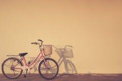 A bicicleta estacionou no tempo de manhã ao lado da parede e da sombra com a Imagem de Stock Royalty Free