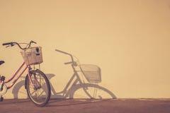 A bicicleta estacionou no tempo de manhã ao lado da parede e da sombra com a Fotos de Stock Royalty Free