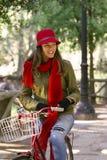 Bicicleta feliz da equitação da jovem mulher no dia do outono foto de stock