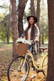 Bicicleta feliz de la bici del montar a caballo de la mujer en parque del otoño de la caída Imagen de archivo