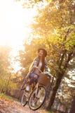 Bicicleta feliz de la bici del montar a caballo de la mujer en parque del otoño de la caída Fotos de archivo libres de regalías