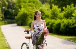 Bicicleta feliz del fixie del montar a caballo de la mujer en parque del verano Imagen de archivo libre de regalías