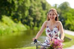 Bicicleta feliz del fixie del montar a caballo de la mujer en parque del verano Foto de archivo