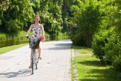 Bicicleta feliz del fixie del montar a caballo de la mujer en parque del verano Foto de archivo libre de regalías