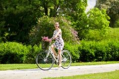 Bicicleta feliz del fixie del montar a caballo de la mujer en parque del verano Fotografía de archivo