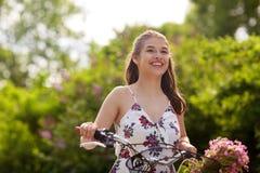 Bicicleta feliz del fixie del montar a caballo de la mujer en parque del verano Fotos de archivo libres de regalías