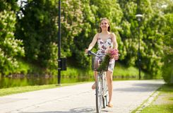 Bicicleta feliz del fixie del montar a caballo de la mujer en parque del verano Fotos de archivo