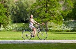 Bicicleta feliz del fixie del montar a caballo de la mujer en parque del verano Fotografía de archivo libre de regalías
