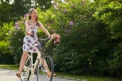 Bicicleta feliz del fixie del montar a caballo de la mujer en parque del verano Imágenes de archivo libres de regalías
