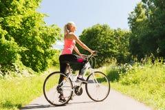 Bicicleta feliz del montar a caballo de la mujer joven al aire libre Foto de archivo