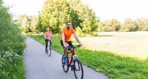 Bicicleta feliz del montar a caballo de los pares al aire libre Imagen de archivo libre de regalías