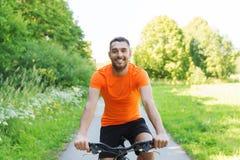 Bicicleta feliz del montar a caballo del hombre joven al aire libre Imágenes de archivo libres de regalías